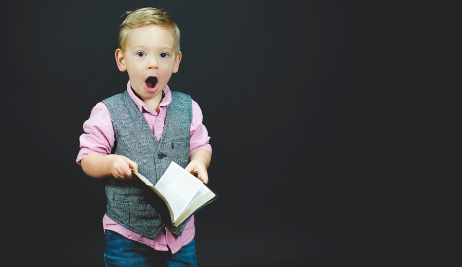 A little boy holding a book with a surprised expression on his face